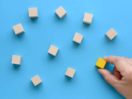 Hand moves a wooden cube to the group of cubes on blue background. Archivio Fotografico