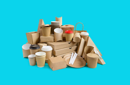 Many Various take-out food containers, pizza box, coffee cups in holder and paper boxes on aqua blue background. 版權商用圖片