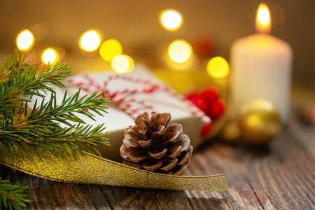 Pine cone, fir branch and gift box on christmas lights and burning candle background