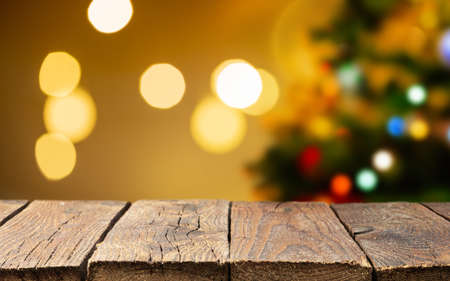 Christmas empty wooden table over christmas tree and blurred light bokeh