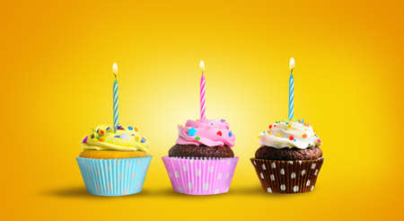Birthday cupcakes with burning candles on a yellow background 版權商用圖片