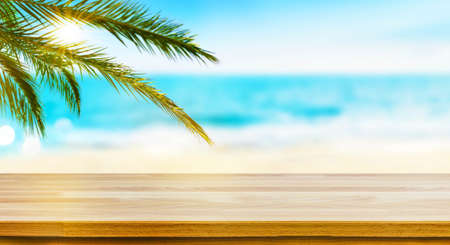 Summer tropical sea with Wooden empty table top sand beach and palm leaves background