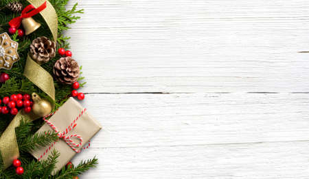 Christmas border composition made of fir branches, cones and gift box on white wooden background