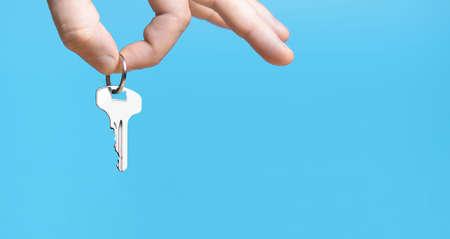 Hand with home key on blue background. 版權商用圖片