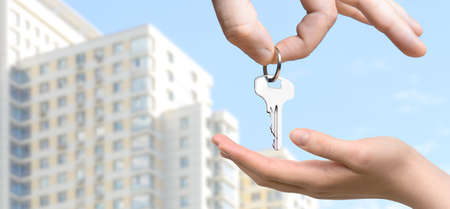 Real estate agent passing the keys to an apartment to the womans hand