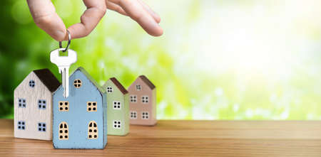 Hand with house key and miniature houses on green nature background 版權商用圖片