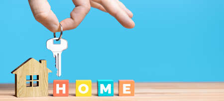 Real estate agents hand hold key above house model on blue background.