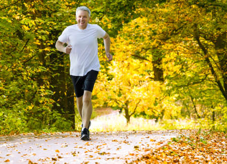 Active mature man running in autumn park 版權商用圖片