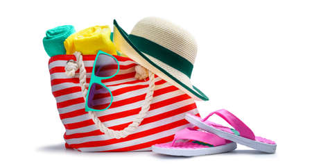 Striped red white beach bag with towel sunglasses flip-flops and hat isolated on white 版權商用圖片