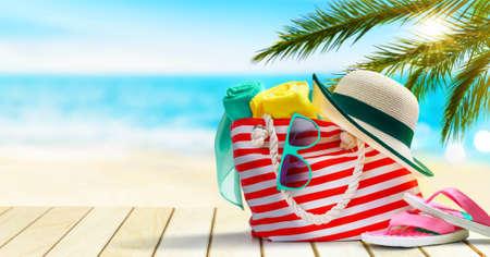 Beach bag, flip flops, hat and sunglasses on a tropical beach.