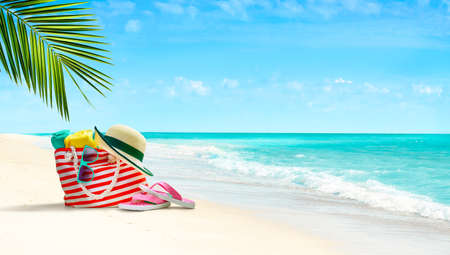 Summer beach bag and accessories on sandy beach and azure sea on background