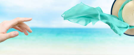 Female straw hat with silk scarf flying away on the wind on sea background.