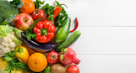 Mixed vegetables and fruits on the white wooden table, directly above, copy space.