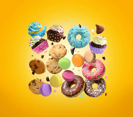 Confectionery and sweets. Donuts, cupcakes, cookies, macarons flying over yellow background. 版權商用圖片