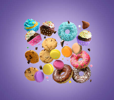 Confectionery and sweets. Donuts, cupcakes, cookies, macarons flying over purple background. 版權商用圖片