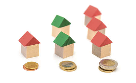 Small wooden houses and coin stacks. Real estate investment concept 版權商用圖片
