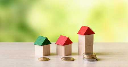 Small wooden houses and euro coin stacks. Real estate investment concept 版權商用圖片