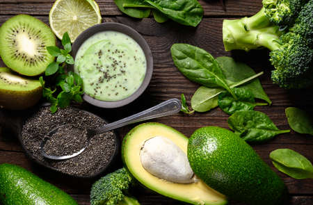 Green smoothie with Healthy ingredients: avocado, spinach, kiwi, chia seeds on wooden table.