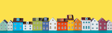 Row of wooden miniature colorful retro houses on a yellow background 版權商用圖片