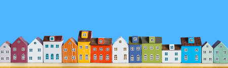 Row of wooden miniature colorful retro houses on blue solid background