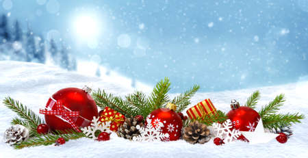 Festive Christmas composition. Decorations with red Christmas balls, gift boxes, cones snowflakes and fir branches in snow on blue winter snowy landscape background with copy space.