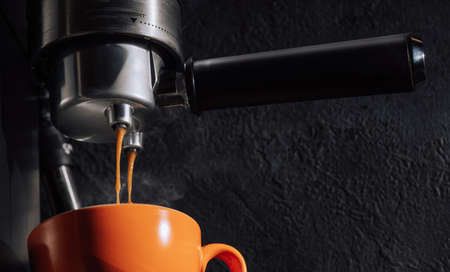 Espresso pouring from coffee machine into orange cup, close up. 版權商用圖片