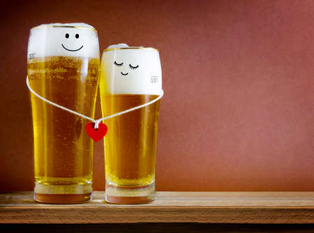 Two glasses of beer with Painted happy couple and red heart on bar counter.