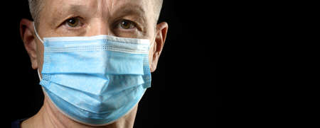 Portrait of man in medical mask looking at camera on black background.