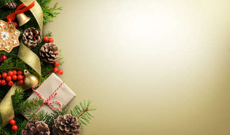 Christmas border composition made of fir branches, cones and gift box on light golden background