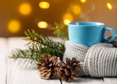 Cup of tea covered with warm scarf with pine cone and fir branch.