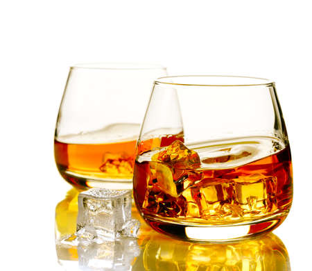 Two glasses of scotch whiskey and ice on a white background