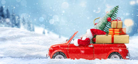 Santa Claus in Red car delivering christmas tree and presents at snowy background. Christmas card
