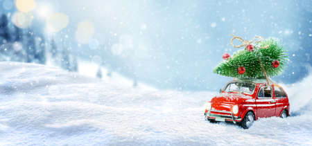 Retro toy car carrying christmas tree on roof in snowy winter forest. Christmas background. Holidays card.