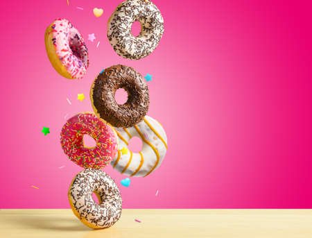 Flying donuts. Mix of multicolored sweet doughnuts with sprinkel on pink background falling on the table.