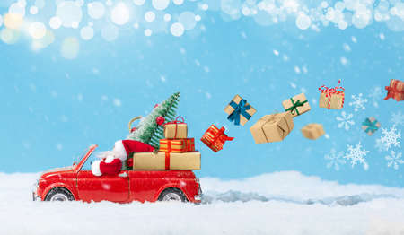 Santa Claus in Red car delivering christmas or New Year gifts at snowy background.