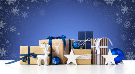 Gift boxes and christmas blue balls on winter abstract background