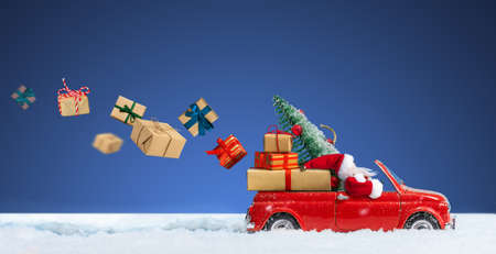 Santa Claus in Red car delivering christmas or New Year gift boxes on a blue snowy background. 版權商用圖片