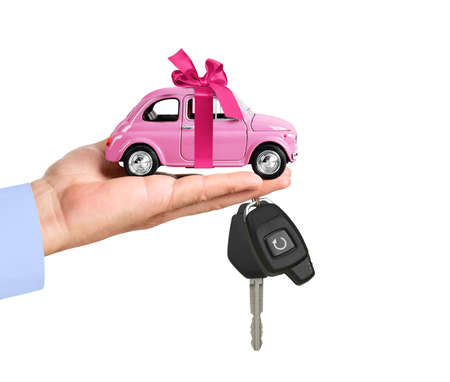 Car with bow and key on dealers palm isolated on white background.