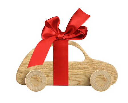 Wooden toy car with ribbon and bow as a gift or present isolated on white 版權商用圖片