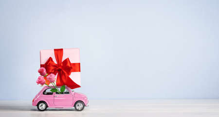 Pink toy car with gift box on a roof and rose flowers on a blue background. Copy space.