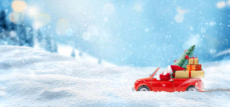 Santa Claus in Red car delivering christmas tree and gifts at snowy background. Christmas card 版權商用圖片