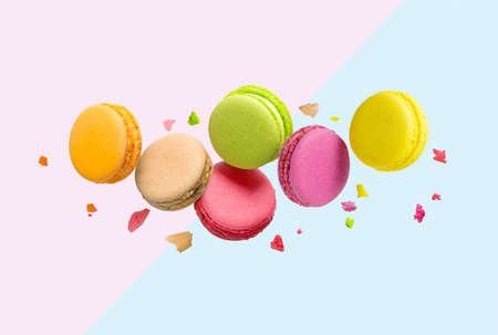 Colorful macaroons flying over blue and pink background.