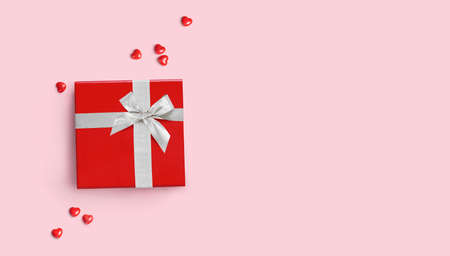 Red gift box with silver ribbon on pink background. Flat lay. Copy space 版權商用圖片