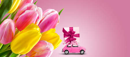 Pink car with gift box on a roof with tulip flowers on a pink background.
