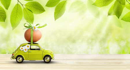Retro car carrying an easter egg on the roof on fresh green spring foliage background.