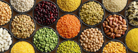 Various colorful legumes and cereals in black bowls background. 版權商用圖片