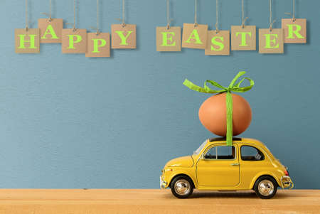 Retro car carrying an easter egg on the roof. Copy space