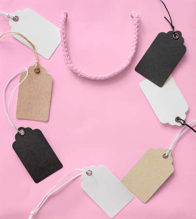 Price tags with rope on pink shopping bag background