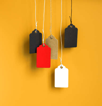 Blank cardboard price tags tied with rope on yellow background
