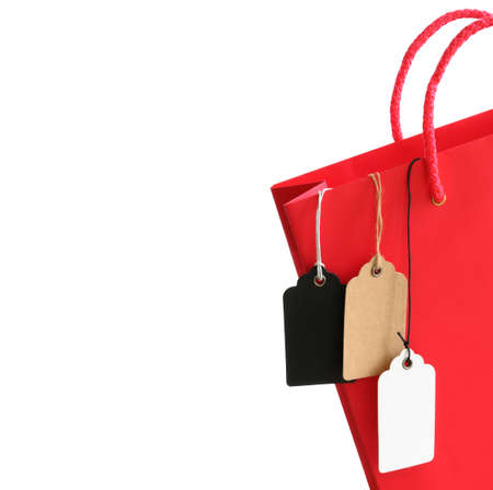 Price tags with rope hanging out of the red shopping bag isolated on white background